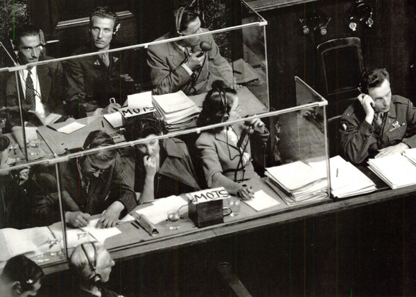 Tlmočníci na norimberských procesoch: vpredu anglickí, vzadu francúzski. Fotografia z knihy Francesca Gaiba: The Origins of Simultaneous Interpretation: The Nuremberg Trial